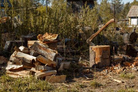 Autumn rural landscape. Firewood and an ax on the background of high grass. Reklamní fotografie