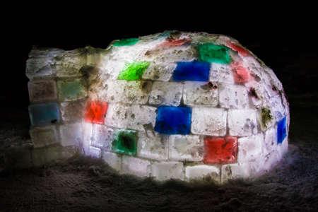Random color igloo, illuminated from the inside on a dark background.
