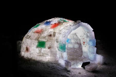 Random color igloo, illuminated from the inside on a dark background. Stock Photo - 124516045
