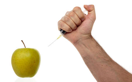 Male hand makes an injection syringe into an apple isolated on white.