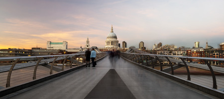 Commuters crossing the Millenium Bridge walking towards St Pauls Cathedral Stock Photo