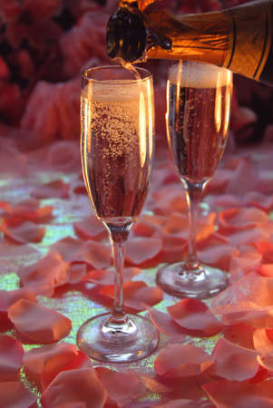 Champagne pouring with soft focus back ground of pink flowers photo