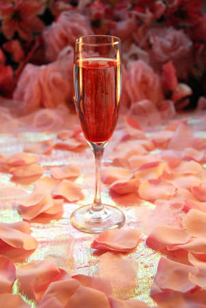 Single glass of pink champagne on a shimmery table surrounded by pink pedals. Background in soft focus Stock Photo - 4010876
