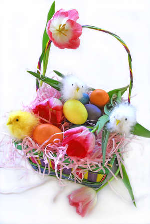Easter Basket filled with colorful eggs and baby chicks and tulips photo