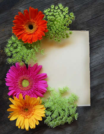Bright flowers on an old page on a weathered wood table photo