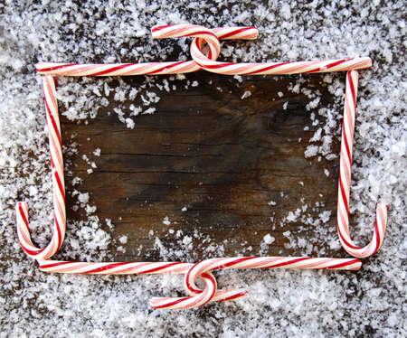 Candy Cane kerst frame op dergelijke hout, omringd door sneeuw