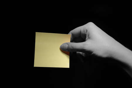 hand holding a blank post-it over black background Stock Photo - 762426