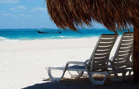 two seats under wicker umbrella photo