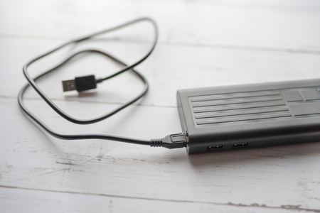 Usb cable with power bank on wooden background