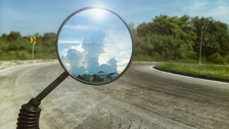 Shot of motorcycle rare view mirror reflecting beautiful sunlight behind white fluffy cloud and road ahead as background. Zdjęcie Seryjne
