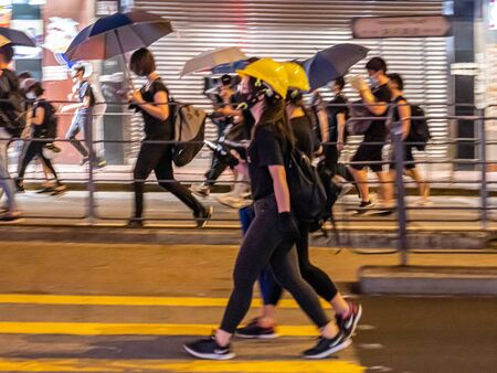 Group of Hong Kong anti-extradition bill protesters marching along street in Wan Chai Area. Hong Kong, 28 July 2019