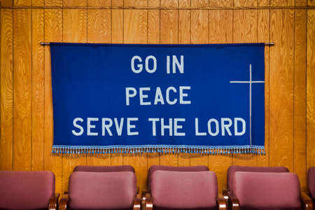 'Go in Peace Serve' the Lord written on Dark Blue Cloth with white cross on the right side, tassels all along the bottom of the cloth, hanging on the wall behind four soft red chairs