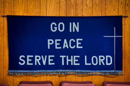 Go in Peace Serve the Lord written on Dark Blue Cloth with white cross on the right side, tassels all along the bottom of the cloth, hanging on the wall behind four soft red chairs