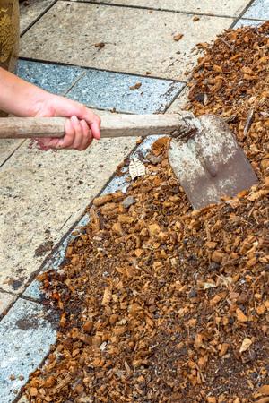 fertile land: man worker using hoe equipment on the soil clay dirt