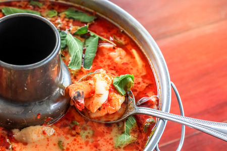 Top view spicy tom yum goong Thai style in the hot pot, spicy soup, a classic spicy lemongrass and shrimp soup recipe from Thailand Standard-Bild