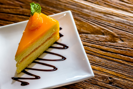 cake plate: piece of orange cheese cake in the white plate on the brown bark background Stock Photo