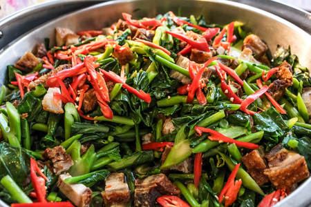 stir up: close up top view stir fry chinese kale with chili and crispy pork