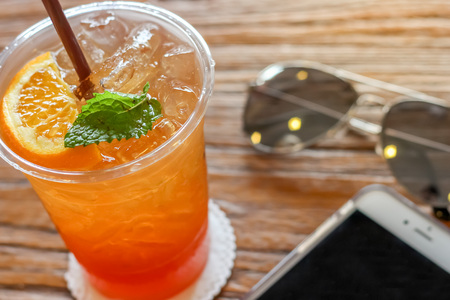 cup of the lemon ice tea with orange and mint on top on the brown bark beautiful texture background with warm light decorated with sunglasses