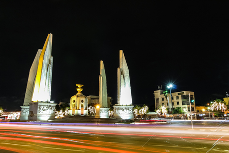 Night view of Democracy Monument in Bangkok, Thailand. The box in the middle represents the holding of Thai constitution and four wing like structures as four branches army forces guarding it. Editorial