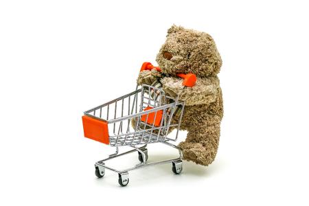 El juguete aislado del oso de peluche está empujando el carro de la carretilla en el fondo blanco