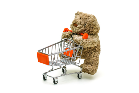 simple store: Isolated Teddy bear toy is pushing the trolley cart on white background