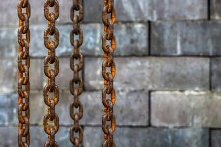 Rusty old chain hanging on over the brick wall background