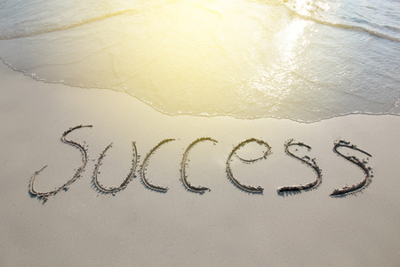 Success word written at the sand beach with sea wave water Reklamní fotografie