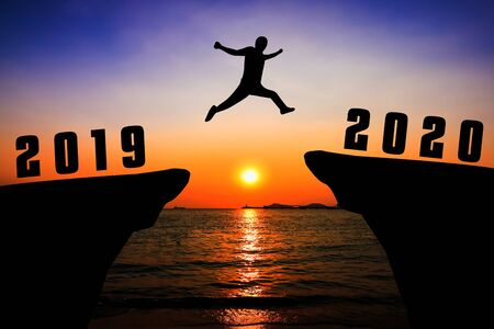 Silhouette young man jumping from 2019 to 2020 years