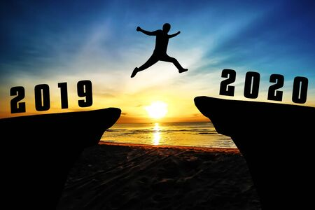 Silhouette young man jumping from 2019 to 2020 years Stock Photo