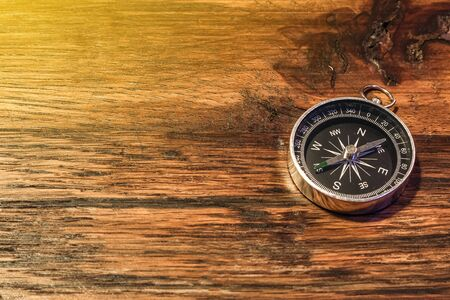 Simple compass on the wooden table with copy space