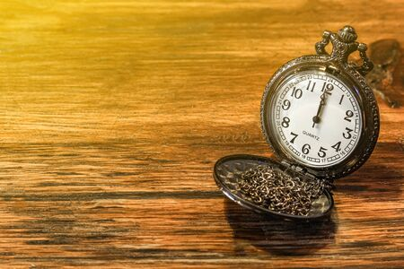 luxury vintage black pocket watch on wooden table, abstract for time concept with copy space, sepia effect