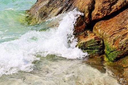 Splash of sea water waves hitting the rocky beach