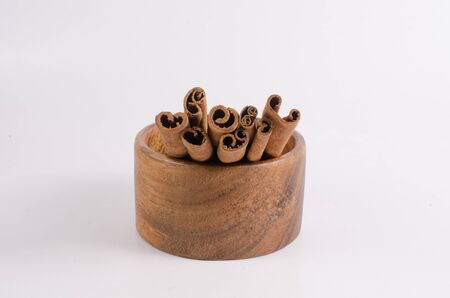 stick of cinnamon: Stick cinnamon on wooden bowl isolated on white Stock Photo