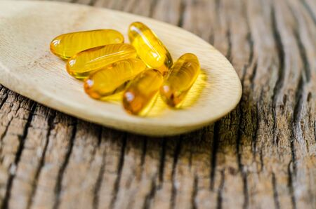 gel capsule: Fish oil on wooden spoon with wooden texture background