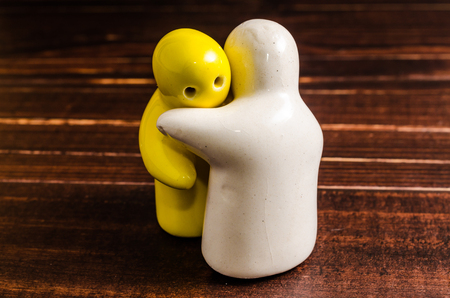 mate married: concept abstract of hugging ceramic dolls on wooden table