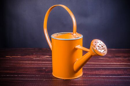bailer: orange garden watering can on wooden board background Stock Photo
