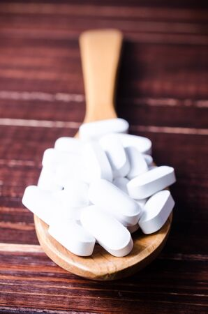 heal sickness: Close up white pills tablets on wooden spoon with wooden board background