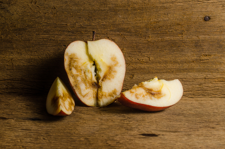 addle: Rotten apple on wooden board background