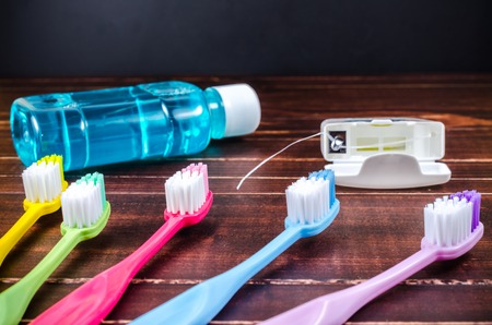 enjuague bucal: Set of colorful toothbrush with mouthwash and dental floss on wooden board Foto de archivo