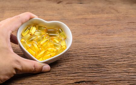 fish oil in heart shape bowl on wooden board background