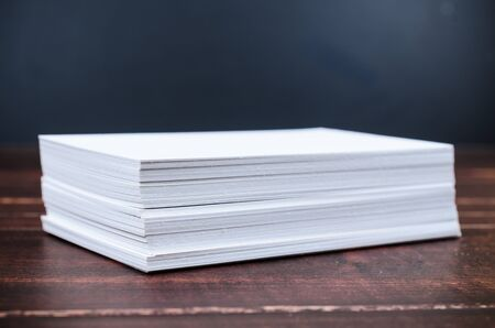 paper stack: Close up stack of white paper on wooden board Stock Photo