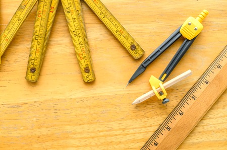 metre: dividers and retro wooden ruler with folding metre ruler measuring on wooden table background Stock Photo
