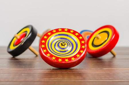 spinning top: Retro colorful wooden spinning top toy on wooden board