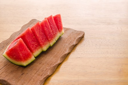 sliced watermelon: Fresh sliced watermelon on wooden board background Stock Photo