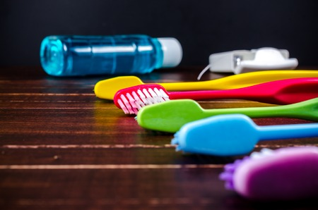 enjuague bucal: Set of colorful toothbrushs with mountwash and dental floss on wooden board Foto de archivo