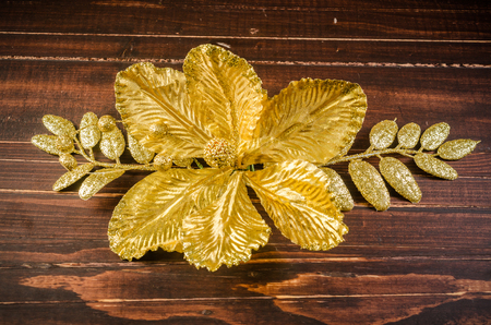 gold flower isolated on wooden board background,gold flower for decoration