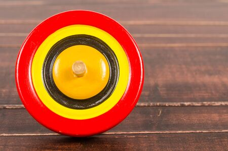 trompo de madera: Retro colorful wooden spinning top toy on wooden board
