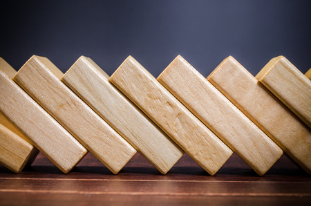 domino effect made up from wooden blocks shape toy on wooden board