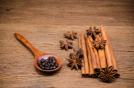 Star anise and cinnamon stick with black pepper on wooden board background,Chinese star aniseed Stock Photo