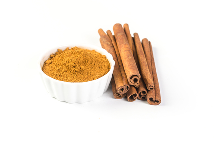 cinnamon powder and cinnamon sticks isolated on white background